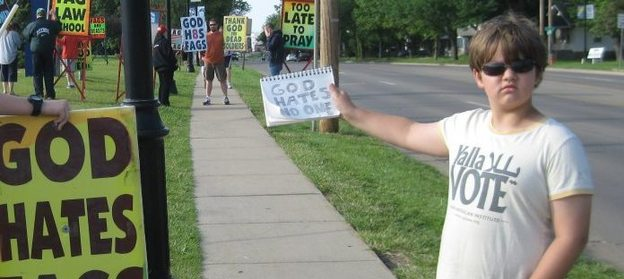 """God hates no one"" written on sign that counter-protestor holds in front of WBC protestors"