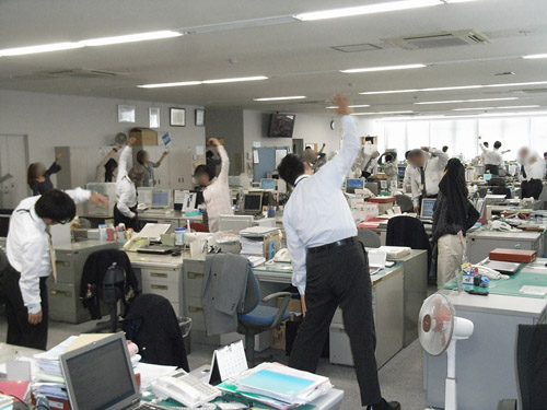 Morning meeting stretches in a Japanese office.